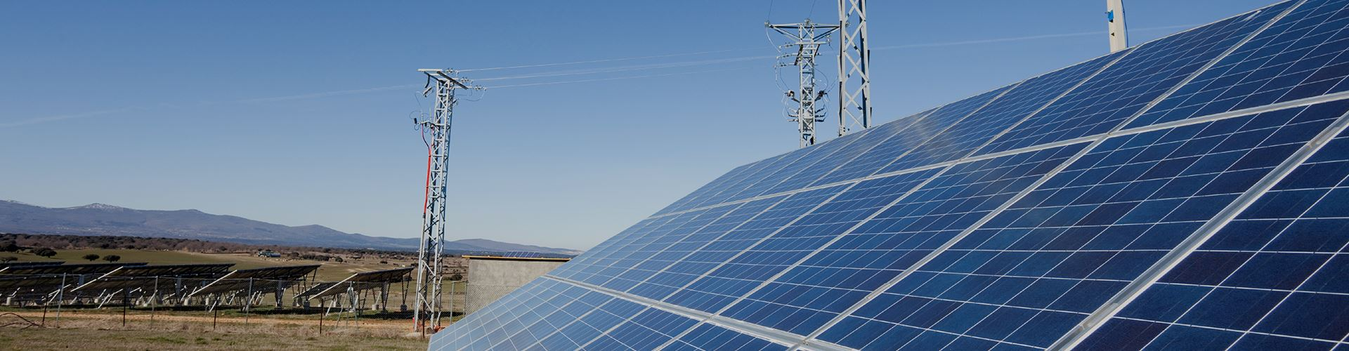 A solar panel array with transmission towers.